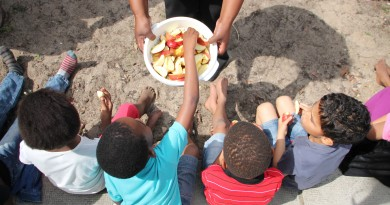 Children being fed red apples as a snack before playtime